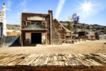 Wooden Old Table Of Free Space For Your Product. Blurred Background Of Wild West City In America.