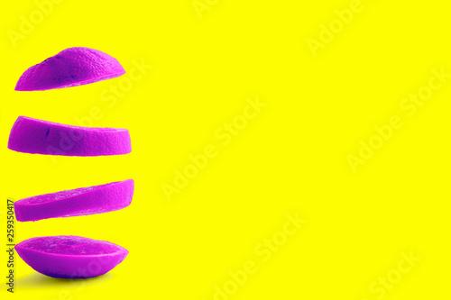 Fotografía  purple orange fruit cut into slices over a yellow background