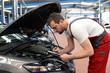 Check am KFZ durch Automechaniker in einer Werkstatt // Check at the motor vehicle by a car mechanic in a workshop