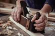 Hands of a carpenter using a vintage plane
