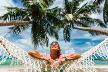 Happy Smile Beautiful Girl In A Straw Hat And Shorts, Striped T-shirt, Lying On A Beach Hammock Between Two Palm Trees, On The Seashore Of A Tropical Island, Traveling Summer Vacation