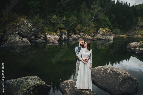 Poster Feeën en elfen Wedding couple travelers on a hill in Norway, Kvalvika. Beautiful view of the beach, Lofoten, Norway.