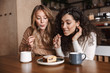 canvas print picture - Excited happy pretty girls friends sitting in cafe drinking coffee eat cake.