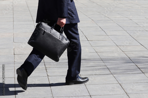 Man with briefcase walking on the street, person in a business suit rushing to a meeting Canvas-taulu