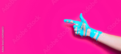 female hand in the paint flowing down the finger shows the direction on a colored background, creative idea of advertising, a gesture of clicking