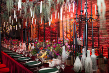 Table Wedding Decor In Red And Black Tones. Pink, Blue And Red Flowers Bouquet And Candles In Bottles.