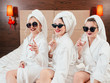 Bachelorette party fun. Cheerful young females in sunglasses, bathrobes and towel turbans with champagne. Bare knees.