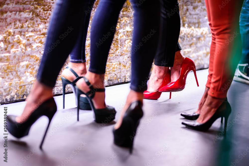 Fototapety, obrazy: Close up of four women's legs in high heels at the disco. Three high heels shoes are black and one red