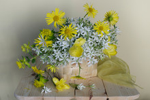 Still Life With White Snowdrops,yellow Daisies In A Basket On A Light Background
