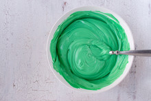 Light Green Buttercream Icing In Bowl With Spoon On White Background Flat Lay