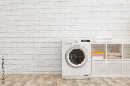 Canvas Print Modern washing machine near brick wall in laundry room interior, space for text