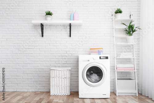Fotografía Modern washing machine near brick wall in laundry room interior, space for text