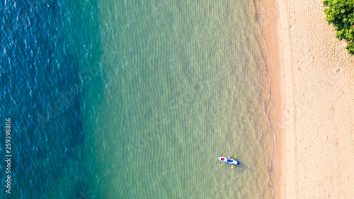 Canvas Print Aerial top view of kayaking around sea with shade emerald blue water and wave fo