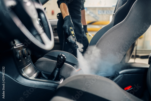 Fototapeta Carwash, worker cleans seats with steam cleaner obraz