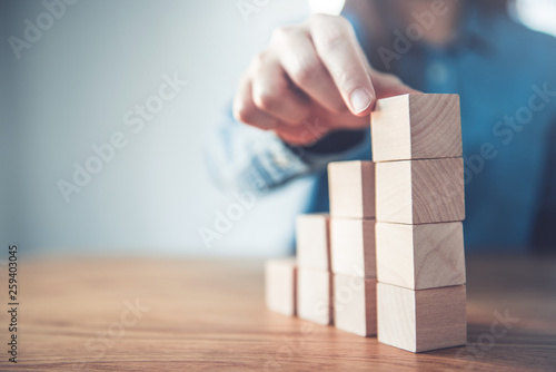 Fotografia  Hand arranging wood cube stacking as step stair