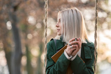 Young Woman With Bleached Hair Holding Coffee Cup While Sitting On Swing