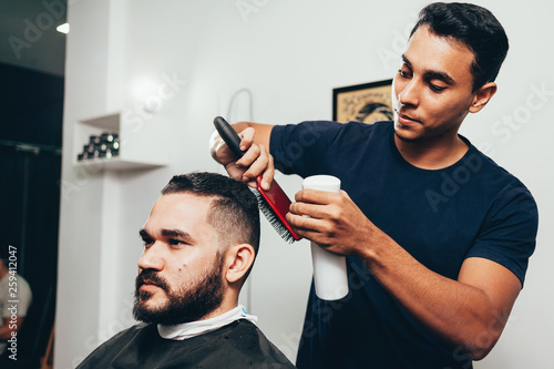 Valokuva  Client during beard and hair grooming in barber shop