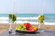 .two glasses with lemon drink and ugly mint leaves on a table with a plate of fruit, on the beach, against the background of the sea