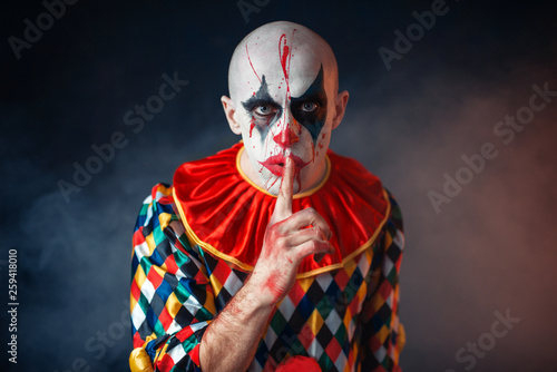 Fotografie, Tablou Portrait of mad bloody clown shows the quiet sign