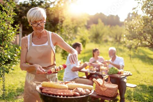 Fototapeta Senior woman cooking meat for family obraz