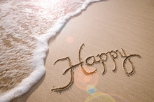 Happy Message Handwritten On The Smooth Sand Of An Empty Beach With An Oncoming Wave And Sunlight Lens Flare