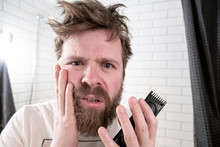 A Man Holds A Trimmer In His H...