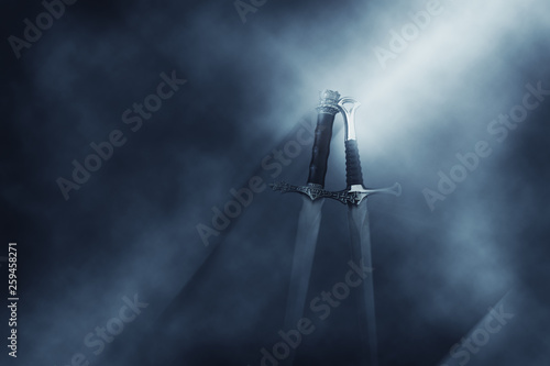 Fotomural mysterious and magical photo of silver sword over gothic black background with smoke