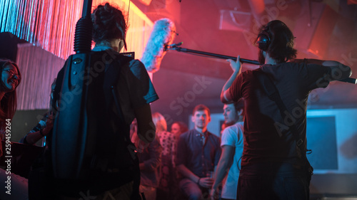 Cameraman and director with a film camera on a film set in a club with red light Fototapete