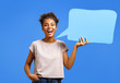 canvas print picture - Happy laughing girl holds blue speech bubble banner. Photo of african american girl wears casual outfit on blue background. Emotions and pleasant feelings concept.
