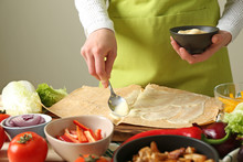 Woman Preparing Tasty Doner Kebab On Table