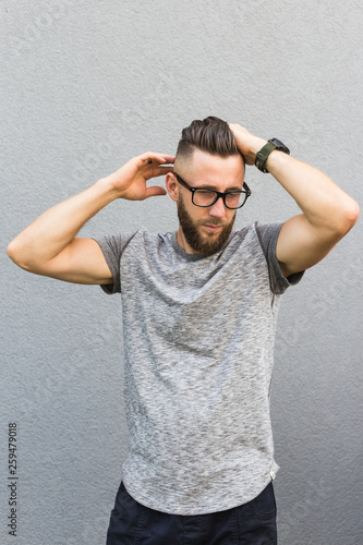 Man with beard holding his head. Isolated on grey background. Wallpaper Mural