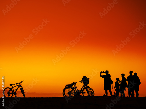 Aluminium Prints Cycling Group of men with bicycles at sunset
