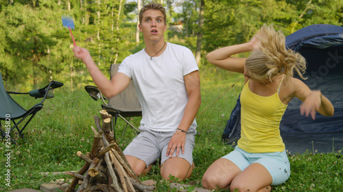 CLOSE UP: Young tourist couple gets annoyed by insects buzzing around them Canvas Print