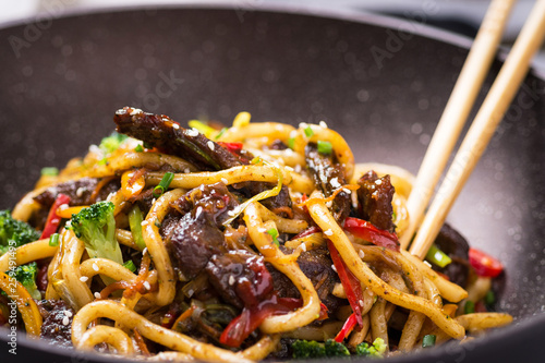 Valokuvatapetti Udon Stir-Fry Noodles with Beef and Vegetables in Wok Pan on Dark Background