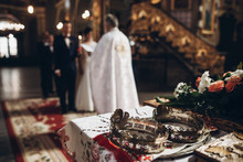 Golden Crowns On Altar And Priest Putting On Golden Wedding Rings On Couple Hand In Church Wedding Ceremony, Religion Traditions.