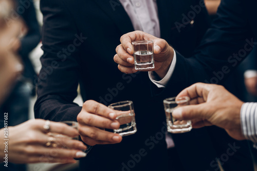 Photographie people toasting holding glasses of vodka cheering at wedding reception, celebration outdoors, catering in restaurant