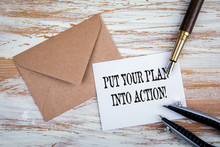 PUT YOUR PLAN INTO ACTION. Paper Letter And Pen On A Wooden Table