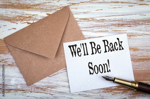 Photo  We'll Be Back Soon. Paper letter and pen on a wooden table