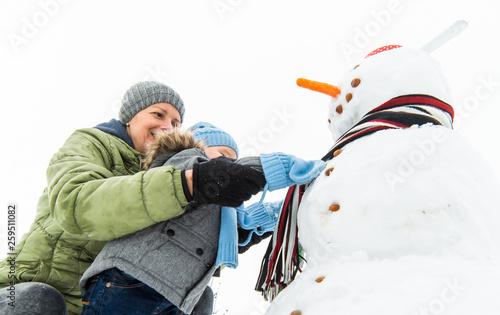 Fényképezés  Smiling baby boy and his mother building snowman