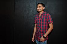 Asian Man In Checkered Shirt Against Dark Background.