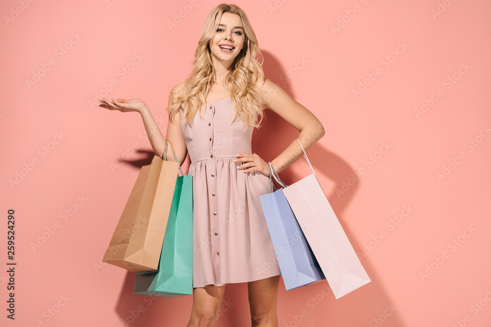 Fototapety, obrazy: smiling and blonde woman in pink dress with shopping bags looking at camera