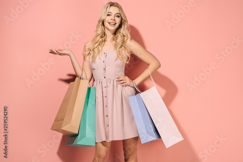 Fotografía  smiling and blonde woman in pink dress with shopping bags looking at camera
