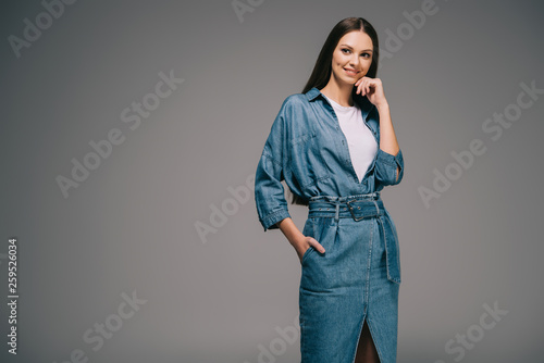smiling and beautiful woman in denim dress with hand in pocket looking away Fototapet