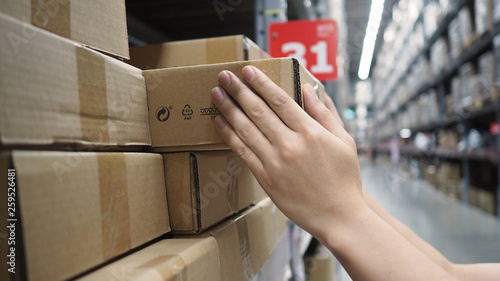 Fotografia Warehouse large storage or cargo for distribution and man's hand is picking up a box