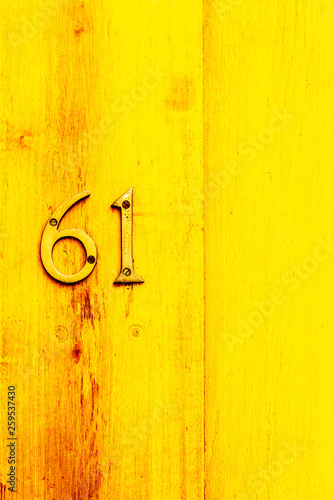 Fotografia  Yellow bright House number 61 with the sixty-one in bronze numbers on a varnishe