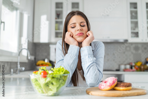 Fototapeta Teenage girl chooses between donuts and vegetable salad. Dilemma concept. obraz