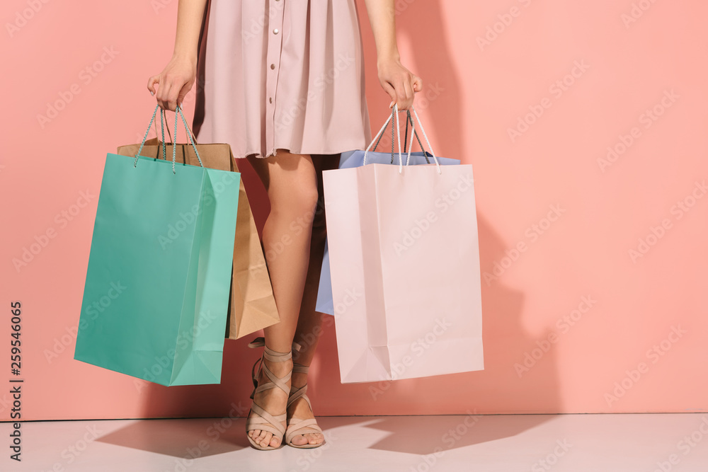 Fototapeta cropped view of woman holding shopping bags on pink background