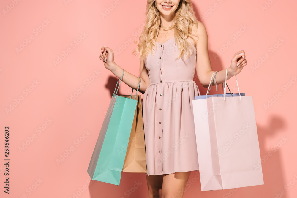 Fototapeta partial view of blonde woman holding shopping bags on pink background