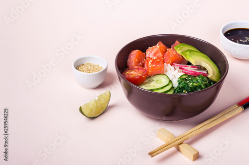 Photo  Hawaiian salmon poke with avocado on pink background, selective focus