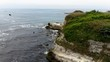 Aerial tracking shot of sea and seashore cliffs in cloudy day, green grass on the rock